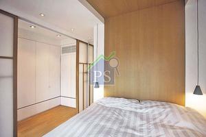 設計師刻意於床背牆鋪以橡木飾板,並將飾板一直延至睡床的天花,成功地將視綫從牆面延至天花,以延伸空間視野。