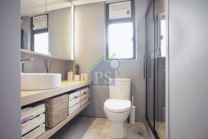 坐廁背牆與鏡櫃下的牆面髹上具高效防水的灰色油漆,地面則是水泥油漆,襯以黑鐵框玻璃浴屏,俐落時尚。