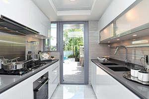 廚房以白色為主調,爐具均採用Siemens品牌,並備有多組廚櫃放置煮食器皿。(本刊攝影組)