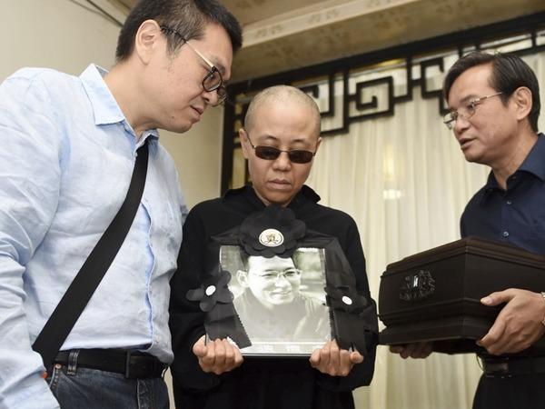 劉霞手捧劉曉波的遺照,臉容憔悴。