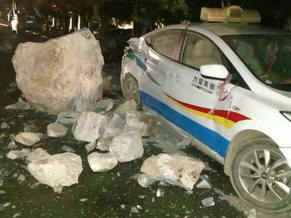 九寨溝地震後,危石塌下損毀路邊汽車。
