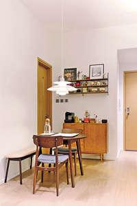 設計師於飯廳的其中一幅牆前放置半腰趟門櫃,櫃身的左右兩側亦預留白牆,櫃的上方則以黑鐵與薄身木板拼合成陳列架,讓戶主陳列餐具及畫作。(相片由被訪者提供)
