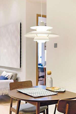 由於長形廳的先天闊度不足,設計師索性放置一張體積纖巧的淺啡色木餐枱,襯以兩張幼身木餐椅。(相片由被訪者提供)