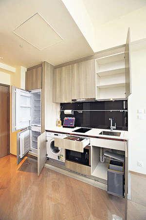 開放式廚房設備齊全,一系列家電包括雪櫃、嵌入式電磁爐、抽油煙機、微波爐、洗衣及乾衣機。(曾有為攝)