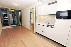 長廳接連22平方呎露台,附有開放式廚房,廚櫃以白色樸素設計。(本刊攝影組)