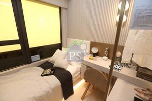 另一間房間擺放單人床、梳妝枱及放置衣物的層架。