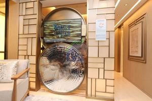 設計師把廳房之間牆身拆除,並以玻璃及金色支架組成隱藏式電視牆。