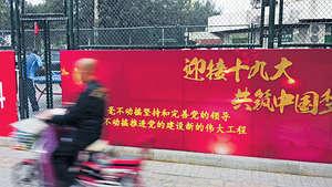 十九大即將於10月18日在北京召開,會議將為中國未來5至10年定下社會及經濟發展目標。圖為北京市民騎電單車駛經「迎接十九大」標語。(中央社資料圖片)