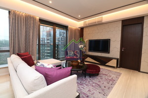 客廳的電視牆身以六角幾何圖案的皮革層疊而成,並擺放一張曲尺形象牙白色梳化。