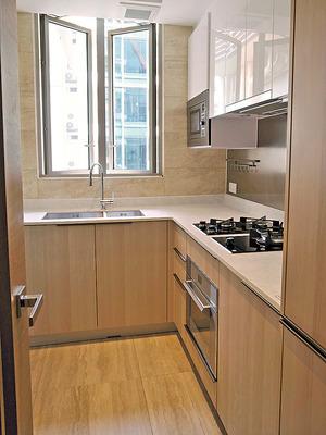 廚房以淺色雲石配合木色廚櫃,曲尺工作枱有助處理食材。(本刊攝影組)