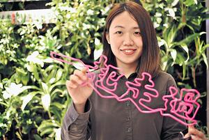 25歲的藝術畢業生陳珮彰認為,其作品仿霓虹燈的效果,加上廣東話字句的設計,能引起共鳴。(林宇翔攝)