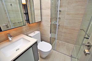 (1座高層A08室)浴室以淺色雲石打造,利用鏡面增加空間感。(本刊攝影組)
