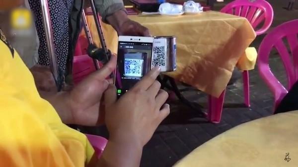 老翁水杯上印有QR Code,善心人可透過手機通訊軟件微信的支付系統,將錢捐給老伯。