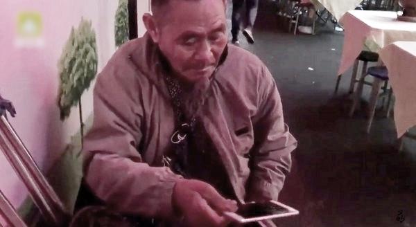 一名撐著拐杖的老翁走向小吃攤乞討,奇怪的是大家沒掏錢,反而是拿出手機。