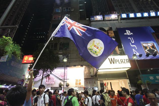 昨夜在旺角鬧市街頭聚集觀看電視、手機直播港中大戰的市民,有人舉起港英旗幟。